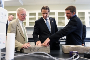 Photo (L-R):  Robert M. Simpson, President & Chief Executive Officer, CenterState CEO; Dr. Cornelius B. Murphy, Jr., President, SUNY-ESF; NYS Governor Andrew M. Cuomo; and Dan Montoney, Chief Technology Officer / Owner, Rapid Cure Technologies, demonstrating a UV coating system startup.